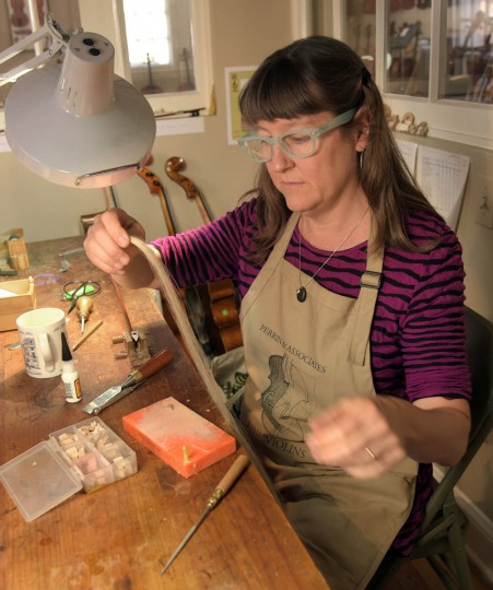 Craftsperson Erika Grant prepares horse hair to re-hair a bow at Perrin and Associates Fine Violins. (Algerina Perna/Baltimore Sun)