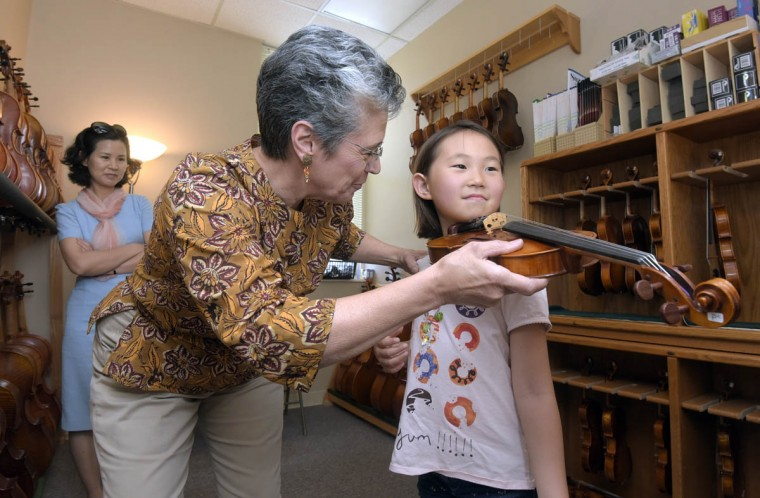Carolyn Foulkes determines the proper size of a violin for Tessa Ahn, 7, from Woodstock, MD, as Tessa's mother, Misu Ahn, looks on from left. Tessa is beginning an introductory to violin class this summer. Perrin and Associates Fine Violins makes, repairs and restores violins and cellos for the aspiring to the accomplished musician. (Algerina Perna/Baltimore Sun)