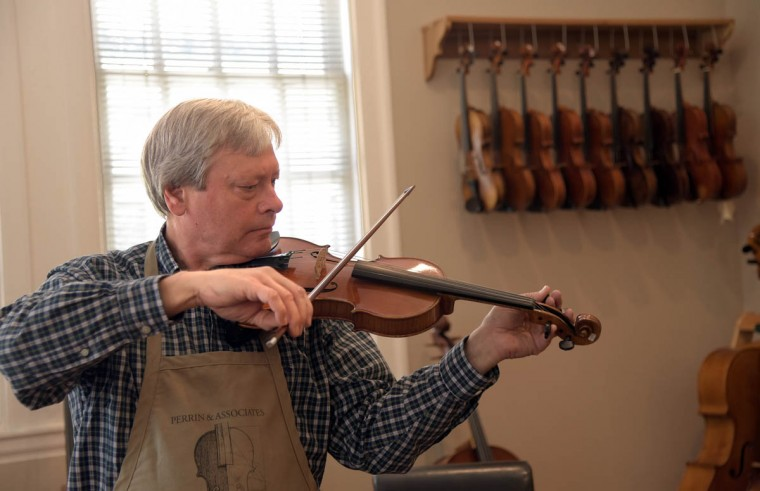 """Rodger Perrin, founder of Perrin and Associates Fine Violins, tunes a violin. Perrin says, """"One of the real pleasures of this business is that we work with musicians of every level. So it's very gratifying to be introducing a beginning violinist or cellist to the very first instrument they'll ever hold. It's equally exciting to do adjustments with some of the best players in Baltimore and nationally."""" (Algerina Perna/Baltimore Sun)"""