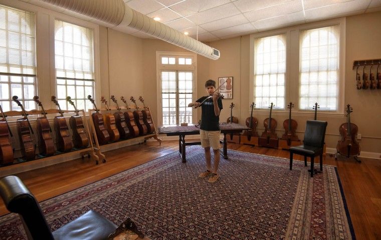 As though the spacious showroom could not become any more pleasing with its high ceilings, numerous windows, oriental carpet and walls lined with stringed instruments, the sound of a violin pierces the silence, making the room come alive with music. Conor Chaikowsky, 15, tries out violins in one of two showrooms at Perrin and Associates Fine Violins. (Algerina Perna/Baltimore Sun)