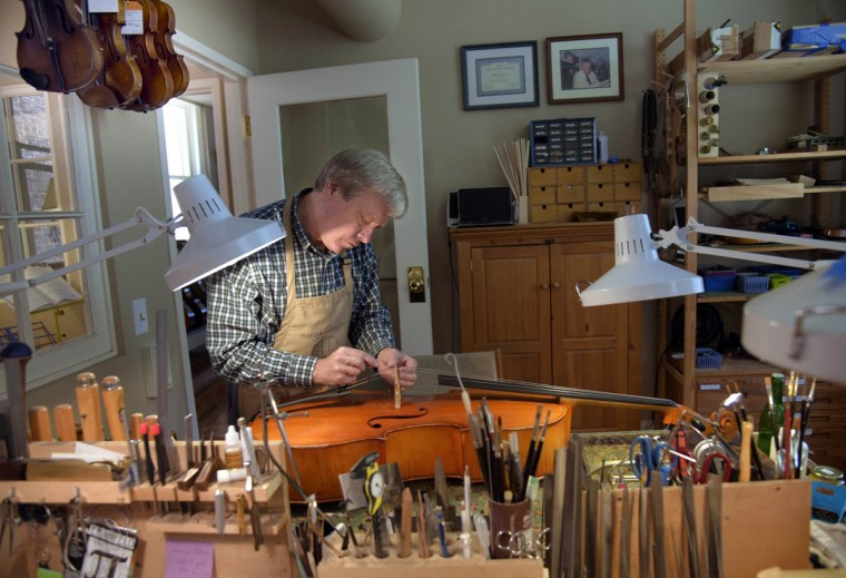 """Perrin & Associates founder Rodger Perrin cuts string channels for a cello bridge designed and crafted by Perrin. He says, """"I was passionate about Mozart and Beethoven when I was five years old."""" His love for classical music progressed from playing violins to building, restoring and repairing violins, violas and cellos. (Algerina Perna/Baltimore Sun)"""