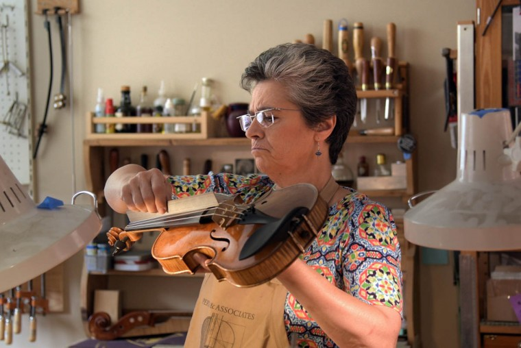 """At Perrin and Associates Fine Violins, primary bow specialist Carolyn Foulkes examines the """"scoop"""" on a violin finger board. (Algerina Perna/Baltimore Sun)"""
