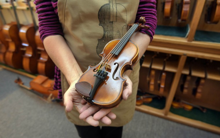 At Perrin & Associates Fine Violins, craftsperson Erika Grant holds the smallest violin, made for a child 4 years old. (Algerina Perna/Baltimore Sun)