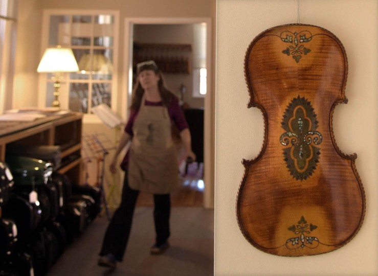 Hanging on the wall At Perrin & Associates Fine Violins is the back of a German violin, circa 1880, with decorative mother-of-pearl inlay as well as other wood inlays. At left, craftsperson Erika Grant heads to another work space in the shop. (Algerina Perna/Baltimore Sun)