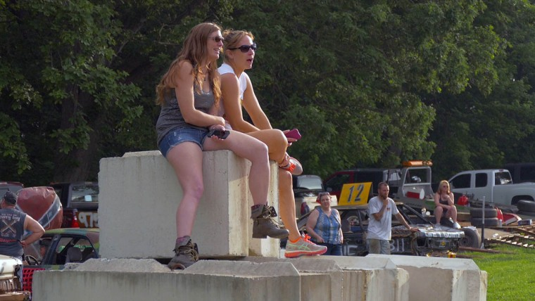 Karen Brensinger (left) of Severn and Emily Schenk of Oxford, PA sit atop concrete barriers to get a view of the competition during Demo Derby Day at Arcadia Volunteer Fire Company's carnival grounds. (Karl Merton Ferron/Baltimore Sun)