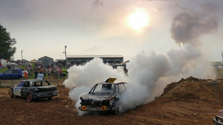 One car, which is started again after flipping over, creates a billow of smoke as the driver gets ready to continue competing during Demo Derby Day at Arcadia Volunteer Fire Company's carnival grounds. (Karl Merton Ferron/Baltimore Sun)