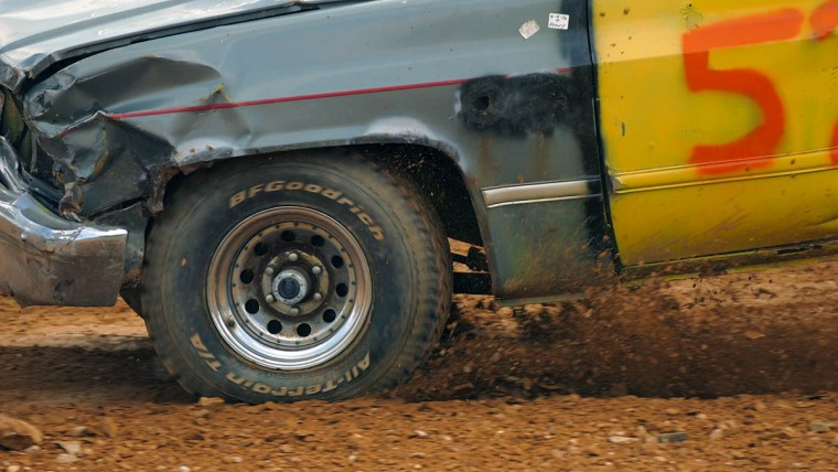 Dented from previous collisions, a pickup truck digs through the soil on the track during Demo Derby Day at Arcadia Volunteer Fire Company's carnival grounds. (Karl Merton Ferron/Baltimore Sun)