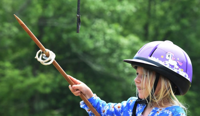 Sara Alexander, 5, of Whiteford, is successful in spearing two rings during lead line jousting in which her horse is led by a walker through the course. (Kenneth K. Lam, Baltimore Sun)