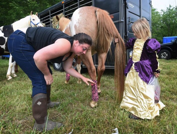 Robin Thomas, left, of Delta, Pa., helps 5-year-old Sara Alexander, of Whiteford, dress up her mount with polo wraps before parading in Amateur Jousting Club of Maryland's 2016 Founder's Day Joust at the historic Jerusalem Mill Village. (Kenneth K. Lam, Baltimore Sun)