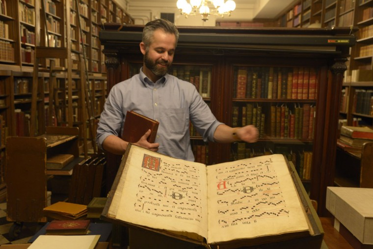 """One of the oldest books in the collection is an antiphonary, or music text from around the 1420s. It would be used as part of the Latin Mass; its large size enabled a group of monks could read it all at once. The antiphonary would have required a small herd of calves to produce enough vellum. """"It's all on calfskin and all done by hand,"""" says Espinoza. """"One monk would have drawn all the lines, another one would have put in all the letters. But we tend to forget in our very fast-paced world that even the act of creating this – the concentration and the meditation and the dedication to create it -- was itself an act of prayer, an act of worship."""" (Christina Tkacik/Baltimore Sun)"""