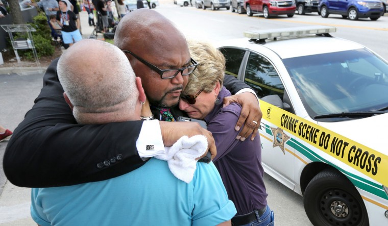 Kelvin Cobaris, a local clergyman, consoles Orlando City Commissioner Patty Sheehan, right, and Terry DeCarlo, an Orlando gay rights advocate, as they arrive on the scene near Pulse nightclub in Orlando, Fla., on Sunday, June 12, 2016. (Joe Burbank/Orlando Sentinel/TNS)