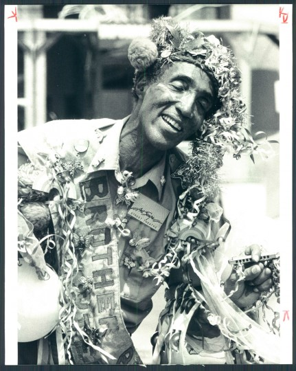 Festooned and beribboned, master storyteller Brother Blue a.k.a. Dr. Hugh Morgan Hill from Cambridge, Massachusetts entertains at Baltimore's second Artscape festival. 1983. (Phillips/Baltimore Sun)