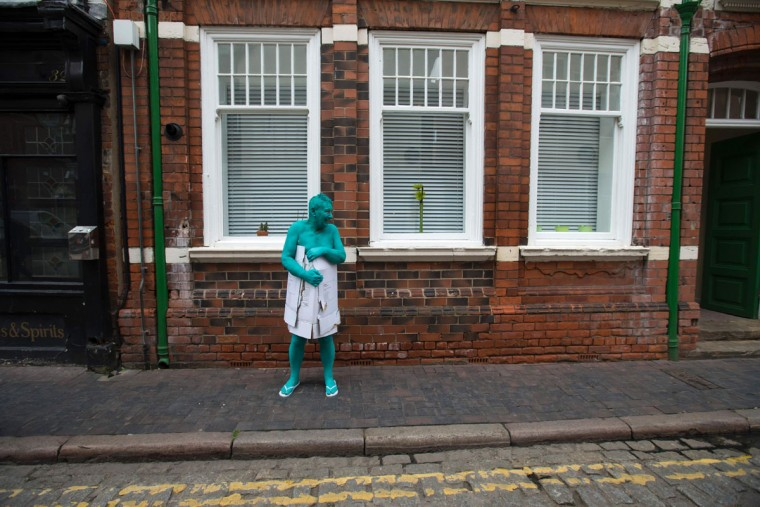 """After taking part in Spencer Tunick's """"Sea of Hull"""" installation, a man covers himself with pieces of cardboard in Kingston upon Hull on July 9, 2016. Over a period of 20 years, the New York based artist has created over 90 art installations in some of the most culturally significant places and landmarks around the world including the Sydney Opera House, Place des Arts in Montreal, Mexico City, Ernest Happel Stadium in Vienna and Munich in Germany. (AFP PHOTO / JON SUPER)"""