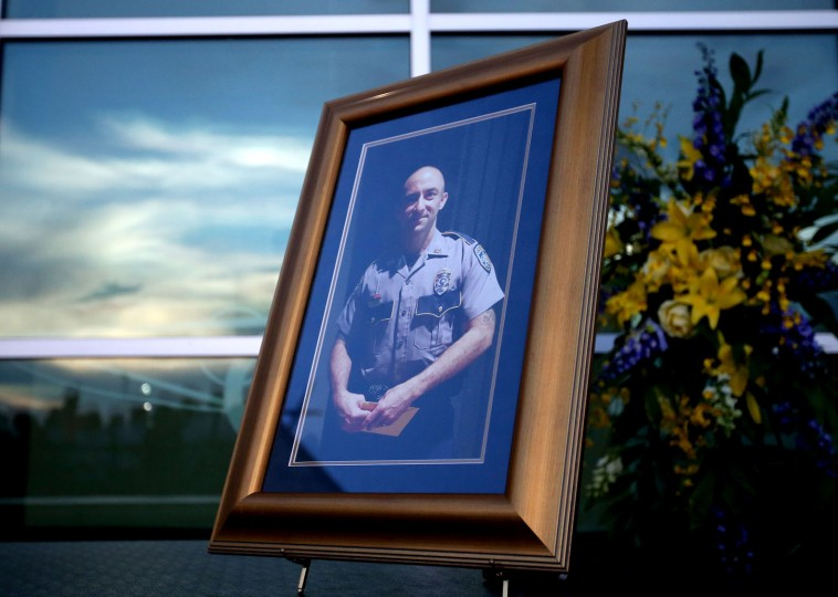 A picture of slain officer Matthew Gerald is placed at a memorial on July 18, 2016 in Baton Rouge, Louisiana. Officer Gerald, along with two other police officers, was shot and killed after gunman Gavin Long ambushed them on Sunday morning in front of the B-Quik gas station in Baton Rouge. (Photo by Sean Gardner/Getty Images)