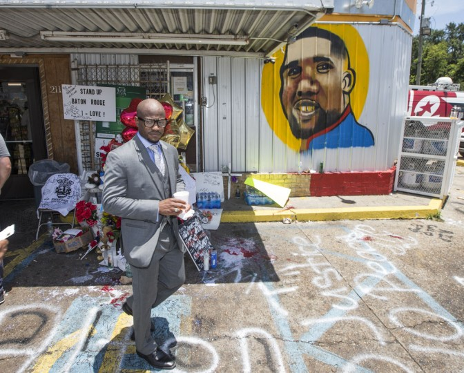 Attorney L. Chris Stewart passes by a memorial for Alton Sterling after speaking to the media in front of the Triple S Mart on July 7, 2016 in Baton Rouge, Louisiana. Stewart and fellow attorneys are representing Alton Sterling's family, Quinyetta McMillon and 15 year-old son Cameron Sterling, after Sterling was shot by a police officer in front of the Triple S Food Mart in Baton Rouge on July 5th, leading the Department of Justice to open a civil rights investigation. (Photo by Mark Wallheiser/Getty Images)