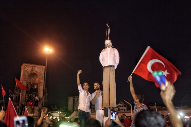 "ISTANBUL, TURKEY - JULY 18: Supporters of Turkish President Tayyip Erdogan hold an effigy of U.S.-based cleric Fethullah Gulen during a pro-government demonstration in Istanbul's central Taksim Square on July 18, 2016 in Istanbul, Turkey. Clean up operations are continuing in the aftermath of Friday's failed military coup attempt which claimed the lives of more than 232 people. In raids across Turkey 7,543 people have been arrested in relation to the failed coup including high-ranking soldiers and judges, Turkey's PM Binali Yildirim has said. The Turkish government says the coup was masterminded by Fethullah Gulen, a Muslim cleric based in the United States who has a wide following in Turkey. U.S. State Department says hours ago, ""U.S. has not made assessment of Turkish cleric Gulen's possible involvement in coup."" (Photo by Kursat Bayhan/Getty Images)"
