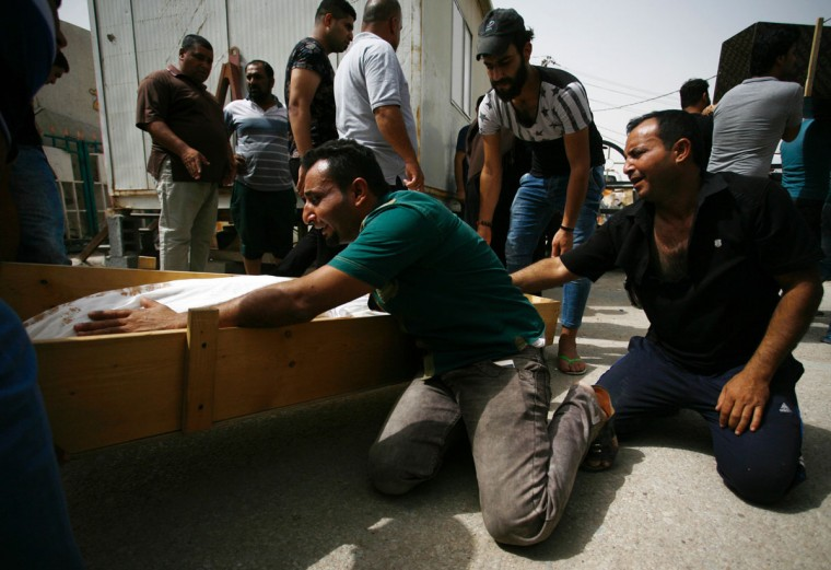 Iraqi men mourn over a body after they lost five members of their family in a suicide bombing that ripped through Baghdad's busy shopping district of Karrada, during their funeral in the holy Iraqi city of Najaf on July 3, 2016. The blast hit the Karrada district early in the day as the area was packed with shoppers ahead of this week's holiday marking the end of the Muslim fasting month of Ramadan, killing at least 75 people in the deadliest single attack this year in Iraq's capital.(AFP PHOTO / Haidar HAMDANI)