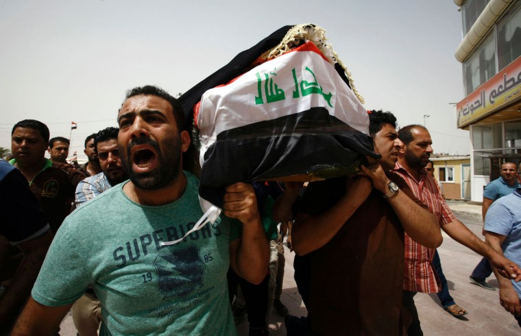 Iraqi men carry a coffin in the holy Iraqi city of Najaf on July 3, 2016, during a funeral procession for the victims of a suicide bombing that ripped through Baghdad's busy shopping district of Karrada. The blast hit the Karrada district early in the day as the area was packed with shoppers ahead of this week's holiday marking the end of the Muslim fasting month of Ramadan, killing at least 75 people in the deadliest single attack this year in Iraq's capital.(AFP PHOTO / Haidar HAMDANI)