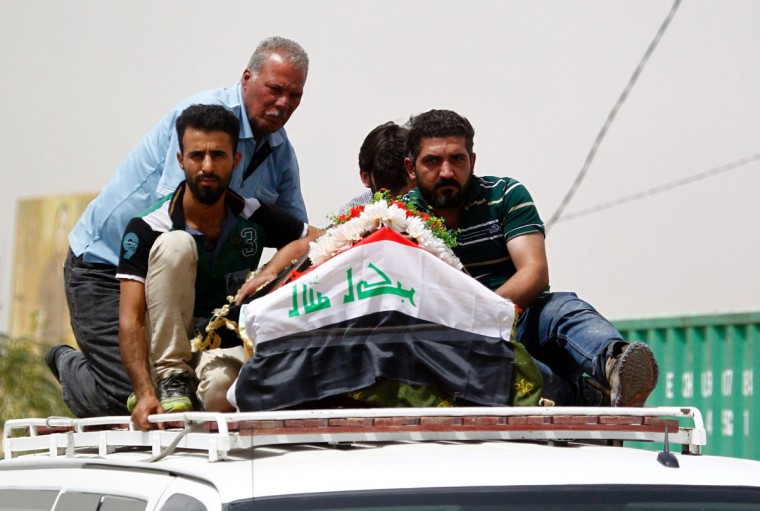 Iraqi men transport a coffin in the holy Iraqi city of Najaf on July 3, 2016, during a funeral procession for the victims of a suicide bombing that ripped through Baghdad's busy shopping district of Karrada. The blast hit the Karrada district early in the day as the area was packed with shoppers ahead of this week's holiday marking the end of the Muslim fasting month of Ramadan, killing at least 75 people in the deadliest single attack this year in Iraq's capital. (AFP PHOTO / Haidar HAMDANI)