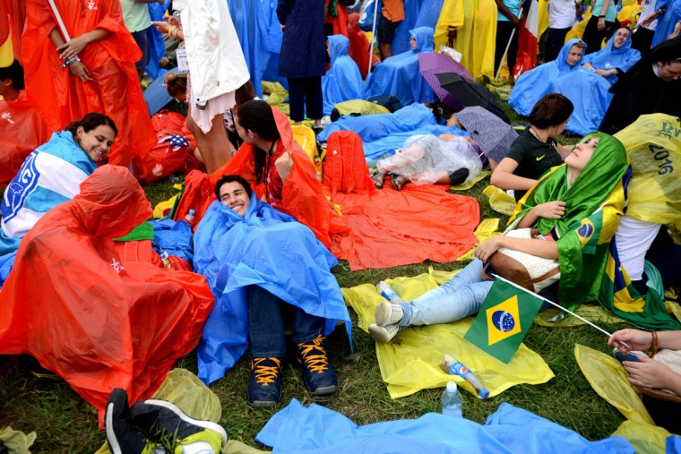 Pilgrims wait in rain for the arrival of Pope Francis to Blonia Park on July 28, 2016 in Krakow to open the World Youth Days. (BARTOSZ SIEDLIK/AFP/Getty Images)