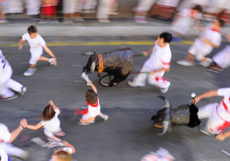 "Children run during the ""encierro txiki"" (small bull run) of the San Fermin Festival in Pamplona, northern Spain, on July 8, 2016. On each day of the festival six bulls are released at 8:00 a.m. (0600 GMT) to run from their corral through the narrow, cobbled streets of the old town over an 850-meter (yard) course. Ahead of them are the runners, who try to stay close to the bulls without falling over or being gored. / (AFP Photo/Ander Gillenea)"
