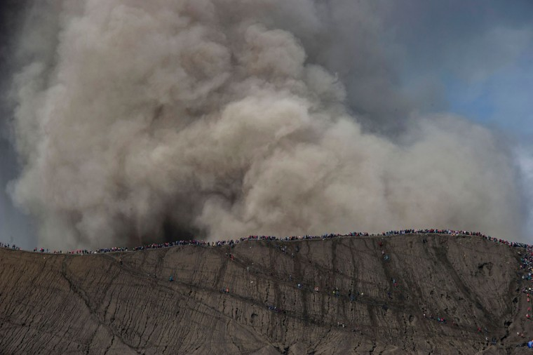 Hindu devotees from the Tengger tribe and tourists climb up to the crater of Mount Bromo during the Yadnya Kasada festival in Probolinggo on July 21, 2016.During the annual Yadnya Kasada festival the Tenggerese climb Mount Bromo, an active volcano, and seek the blessing from the main deity Hyang Widi Wasa by presenting offerings of rice, fruit, livestock and other local produce. / (AFP Photo/Juni Kriswanto)
