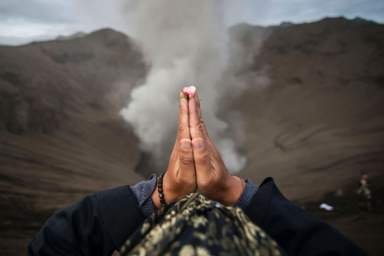 A Hindu devotee of the Tengger tribe prays during the Yadnya Kasada festival, on the crater of Mount Bromo in Probolinggo on July 21, 2016.During the annual Yadnya Kasada festival the Tenggerese climb Mount Bromo, an active volcano, and seek the blessing from the main deity Hyang Widi Wasa by presenting offerings of rice, fruit, livestock and other local produce. / (AFP Photo/Juni Kriswanto)