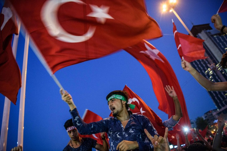 "Demonstrators wave Turkish flags at Taksim square in Istanbul on July 17, 2016 during a demonstration in support to the Turkish government following a failed coup attempt. Turkish authorities pressed on July 17 with a ruthless crackdown against suspects in the failed coup against President Recep Tayyip Erdogan, with 6,000 people detained as he vowed to stamp out the ""virus"" of the putschists. Erdogan also said Turkey could consider reinstating the death penalty following the putsch bid, despite concerns in the international community. (AFP PHOTO / OZAN KOSE)"