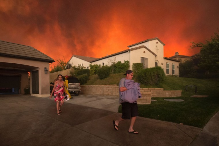 Residents flee their home as flames from the Sand Fire close in on July 23 2016 near Santa Clarita, California. Fueled by temperatures reaching about 108 degrees fahrenheit, the wildfire began yesterday has grown to 11,000 acres. (AFP PHOTO / DAVID MCNEW)