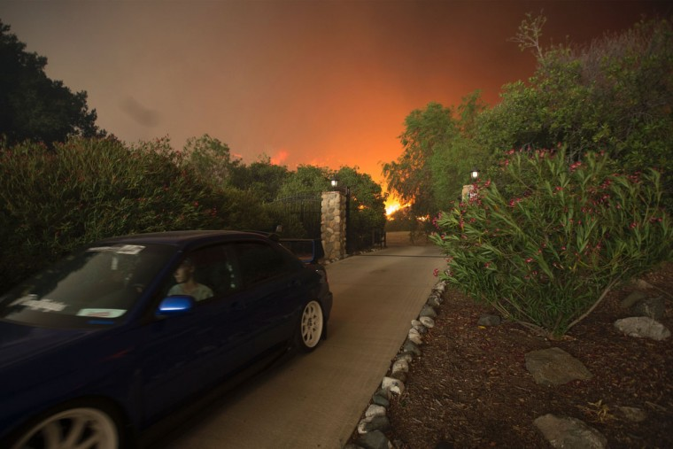 Residents flee as flames close in on their homes at the Sand Fire on July 23 2016 near Santa Clarita, California. Fueled by temperatures reaching about 108 degrees fahrenheit, the wildfire began yesterday has grown to 11,000 acres. (AFP PHOTO / DAVID MCNEW)