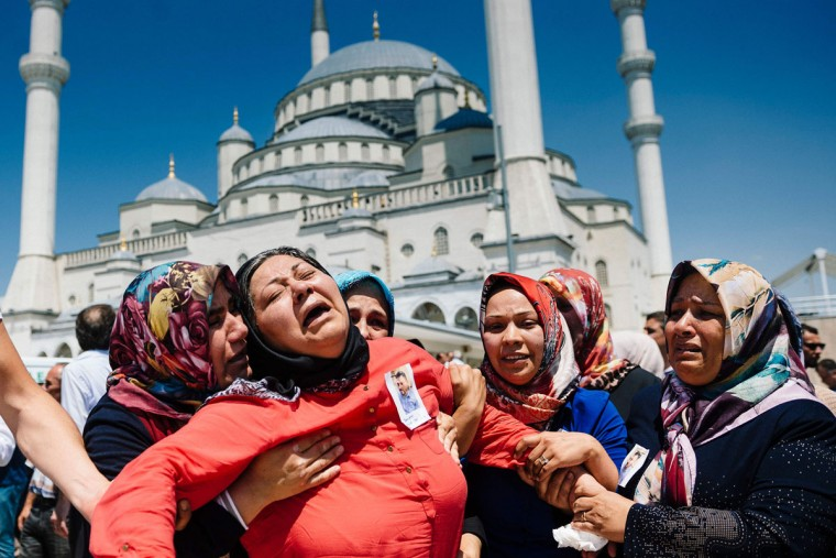 Women react during the funeral ceremony of Sehidmiz Murat Inci, victim of the coup attempt, at Kocatepe Mosque in Ankara on July 18, 2016. Support from the highest echelons in the army helped keep President Recep Tayyip Erdogan in power after the failed coup but July 15's events risk further undermining the military's status as a key player in Turkish politics. Turkey has detained 103 generals and admirals as well as more than 2,800 soldiers accused of supporting July 15's attempted power grab, but most of the military's senior figures stayed loyal to Erdogan. (AFP PHOTO / DIMITAR DILKOFF)