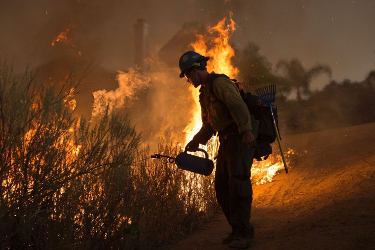 A firefighter with the Texas Canyon Hotshot crew lights a backfire near homes to fight the Sand Fire on July 23 2016 near Santa Clarita, California. Fueled by temperatures reaching about 108 degrees fahrenheit, the wildfire began yesterday has grown to 11,000 acres. (AFP PHOTO / DAVID MCNEW)