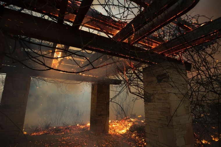 A picnic structure near a home burns during the Sand Fire on July 23 2016 near Santa Clarita, California. Fueled by temperatures reaching about 108 degrees fahrenheit, the wildfire began yesterday has grown to 11,000 acres. (AFP PHOTO / DAVID MCNEW)