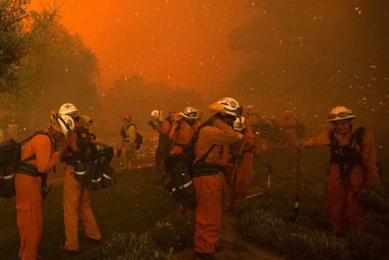 Inmate handcrew firefighters shield themselves from embers and heavy smoke as flames close in on houses at the Sand Fire on July 23 2016 near Santa Clarita, California. Fueled by temperatures reaching about 108 degrees fahrenheit, the wildfire began yesterday has grown to 11,000 acres. (AFP PHOTO / DAVID MCNEW)