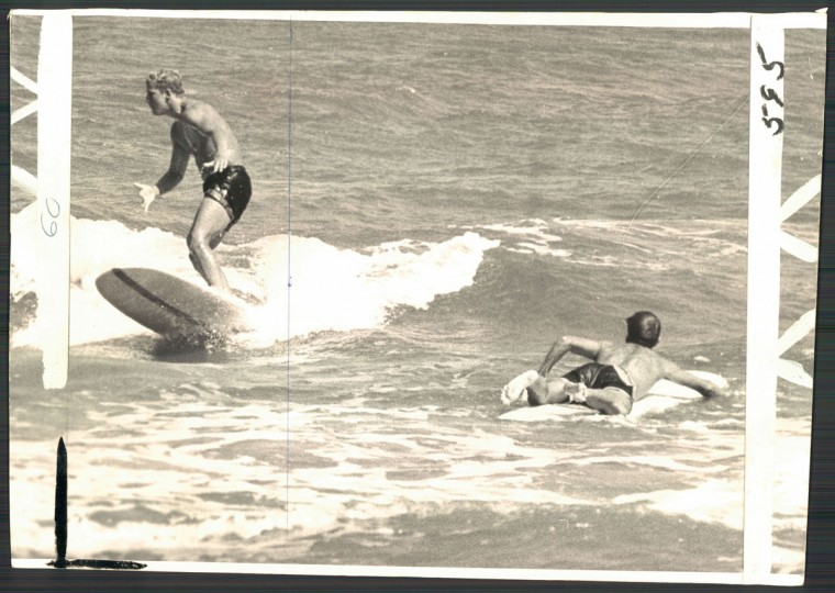 """The Board Riders--Well balanced youth at left rides waves into Ocean City beach while surfboarder at right paddles out to catch another breaker. Some enthusiasts surf the year round."" Ocean City, MD. September 15, 1964. (Cook/Baltimore Sun)"