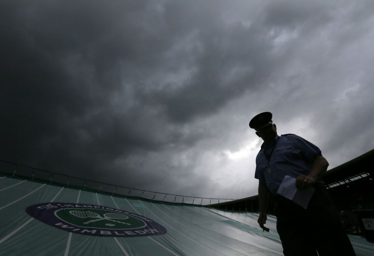 A member of staff stands by a covered out as rain delays play during day five of the Wimbledon Tennis Championships in London, Friday, July 1, 2016. (AP Photo/Tim Ireland)