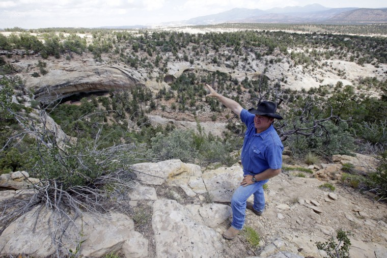 "In this June 23, 2016, photo, rancher Kenny Black points to a rock overhang housing an ancient cliff dwelling, near Blanding, Utah. ""These areas are sacred to me because I've grown up here,"" said Black, who comes from Mormon pioneers who came to the area in the late 19th Century. ""They're part of my history and my culture as well."" (AP Photo/Rick Bowmer)"