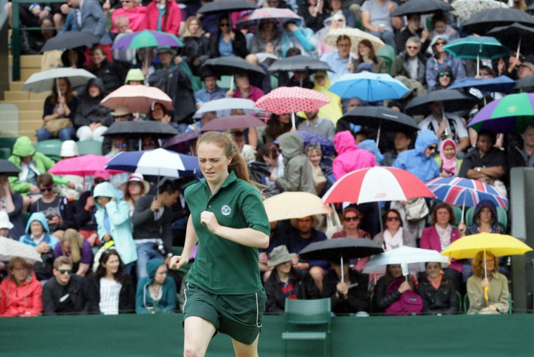 Spectators take shelter under umbrellas as rain delays play on day five of the Wimbledon Tennis Championships in London, Friday, July 1, 2016. (AP Photo/Tim Ireland)
