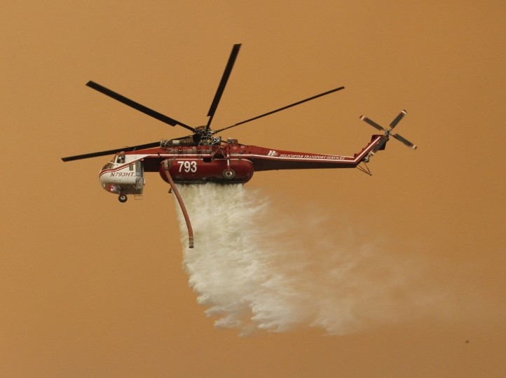 A helicopter drops water on the Sand Fire near Wildlife Waystation on Little Tujunga Canyon Road, Calif., on Saturday, July 23, 2016. (Katharine Lotze/The Santa Clarita Valley Signal via AP)