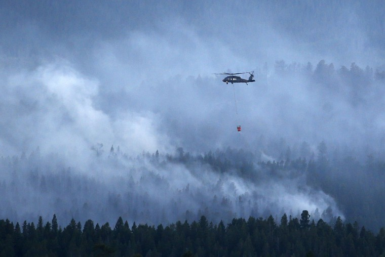 A military Blackhawk helicopter carries a water bucket while helping crews on the ground battle the Cold Springs Fire near Nederland, as viewed from Sugarloaf, Colo., Sunday, July 10, 2016. Fire authorities are warning that shifting high winds and high temperatures could put homes in danger. The fire that started on Saturday spread quickly. (AP Photo/Brennan Linsley)