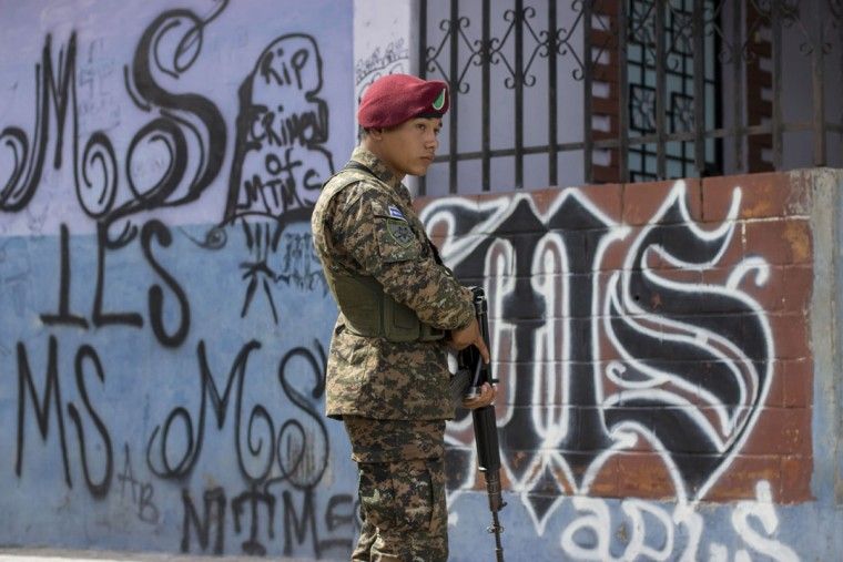 In this June 21, 2016 photo, an army paratrooper patrols the April 22 neighborhood in Soyapango, El Salvador, as part of extraordinary security measures to dismantle gangs. After becoming the world's murder capital last year and posting an equally bloody start to 2016, El Salvador has seen its monthly homicide rates fall by about half. The government attributes the drop to a tough military crackdown on the country's powerful gangs, while the gangs themselves claim credit for a nonaggression pact between the three biggest criminal groups. (AP Photo/Salvador Melendez)