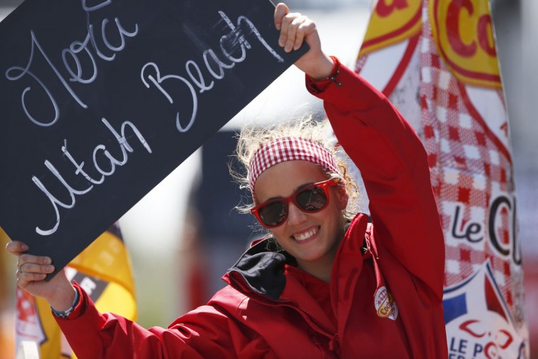 "A girl on a vehicle of the sponsor's parade hold a sign reading ""Thank You Utah Beach"" during the first stage of the Tour de France cycling race over 188 kilometers (116.8 miles) with start in Mont-Saint-Michel and finish in Utah Beach, France, Saturday, July 2, 2016. (AP Photo/Peter Dejong)"