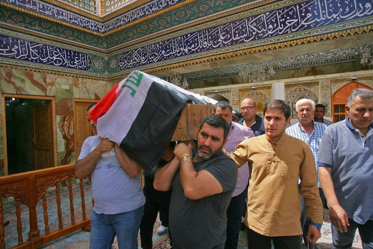 Mourners carry the Iraqi flag-draped coffin of, Talib Hassan, 35, who was killed of bomb in Karada neighborhood, during a funeral procession at the holy shrine of Imam Ali in Najaf, 100 miles (160 kilometers) south of Baghdad, Iraq, Sunday, July 3, 2016. Dozens of people have been killed and more than 100 wounded in two separate bomb attacks in the Iraqi capital Sunday morning, Iraqi officials said. (AP Photo/Anmar Khalil)