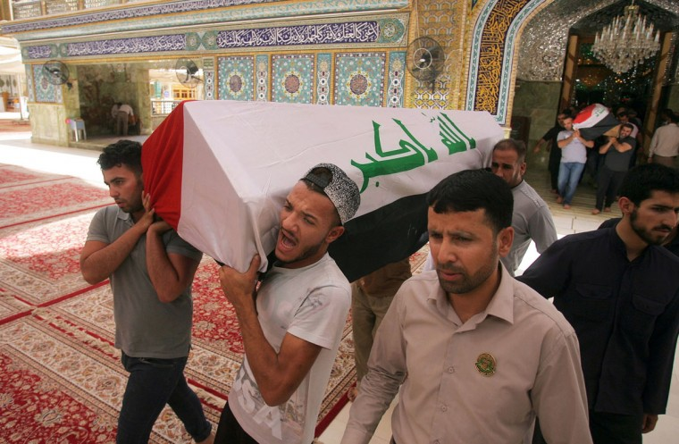 Mourners carry the Iraqi flag-draped coffins of bomb victims, Talib Hassan, 35, and Hamza Jabbar, 37, during their funeral procession at the holy shrine of Imam Ali in Najaf, 100 miles (160 kilometers) south of Baghdad, Iraq, Sunday, July 3, 2016. Dozens of people have been killed and more than 100 wounded in two separate bomb attacks in the Iraqi capital Sunday morning, Iraqi officials said. (AP Photo/Anmar Khalil)