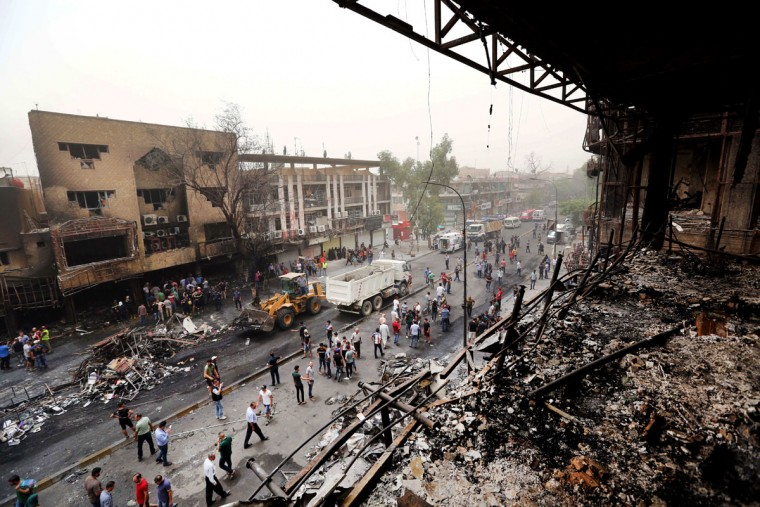 Iraqi security forces and civilians gather at the site after a car bomb hit Karada, a busy shopping district in the center of Baghdad, Iraq, Sunday, July 3, 2016. Dozens of people have been killed and more than 100 wounded in two separate bomb attacks in the Iraqi capital Sunday morning, Iraqi officials said. (AP Photo/Hadi Mizban)