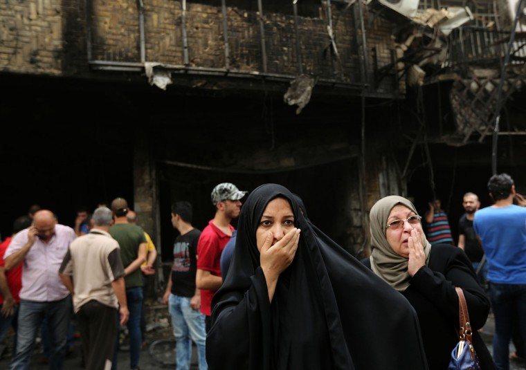 Iraqi women wait for their family members who are missing after a car bomb went off in a commercial area in Karada neighborhood, Baghdad, Iraq, Sunday, July 3, 2016. Dozens of people have been killed and more than 100 wounded in two separate bomb attacks in the Iraqi capital Sunday morning, Iraqi officials said. (AP Photo/Hadi Mizban)
