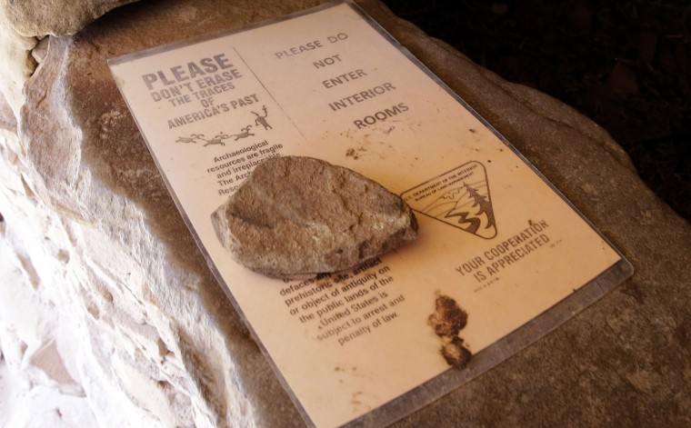 "In this June 22, 2016, photo, a laminated sheet of paper held in place by a loose rock rests inside a series of ancient cliff dwellings that are nestled underneath a spectacular red rock overhang, near Blanding, Utah. ""Don't erase the traces of America's past,"" the signs read. ""Please do not enter interior rooms."" The weathered signs and a similar warning at the trailhead are the only protections in place for these Anasazi ruins easily accessible along a canyon hiking path. (AP Photo/Rick Bowmer)"