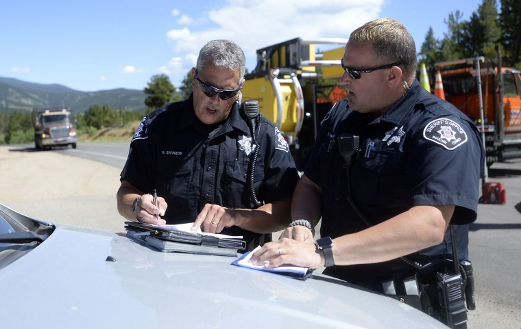Boulder County Sheriff's Deputies Mark Spurgeon, left, and Dave Salaman work on logistics for allowing evacuees time to get medications from their homes near Ridge Road while crews battle the Cold Springs Wildfire on Monday, July 11, 2016, near Nederland, Colo. (Jeremy Papasso/Daily Camera via AP)