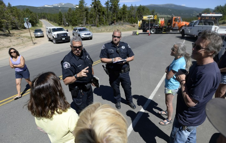 Boulder County Sheriff's deputies Mark Spurgeon, center left, and Dave Salaman talk with evacuees before allowing them to get medications and belongings from their homes near Ridge Road while crews battle the Cold Springs Wildfire on Monday, July 11, 2016, near Nederland, Colo. (Jeremy Papasso/Daily Camera via AP)
