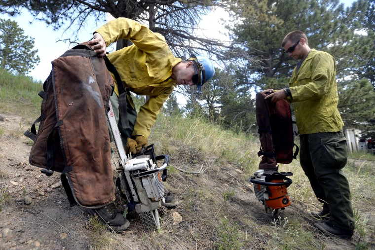 Flathead Hot Shots firefighters Danny Bondurant, left, and Pat McChesney prepare their chainsaws before heading in to battle the Cold Springs Wildfire on Monday, July 11, 2016, near Nederland, Colo. (Jeremy Papasso/Daily Camera via AP)